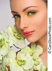 Beautiful make-up. Beautiful young women with make-up looking at camera while isolated on grey