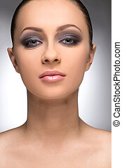 Beautiful make-up. Portrait of confident young women with make-up looking at camera while isolated on grey