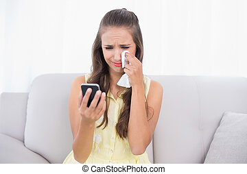Crying attractive brunette holding mobile phone and tissue...