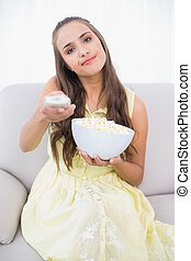 Content young brunette pressing remote in bright living room