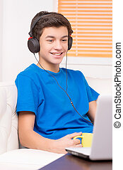 Teenager at the computer. Cheerful teenage boy in headphones looking at the computer monitor and smiling