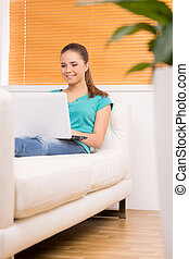 Girl with laptop. Cheerful teenage girl using computer and smiling