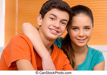 Friends. Cheerful teenage boy and girl sitting close to each...