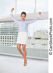 Excited brunette businesswoman jumping and cheering in...