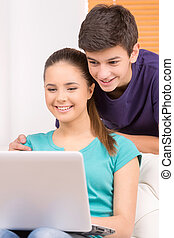 Teenagers. Two cheerful teenagers looking at computer monitor and smiling