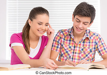 Studying together. Cheerful teenage boy and girl sitting...