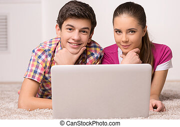 Leisure time. Two cheerful teenagers using computer together...