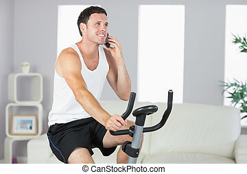 Smiling sporty man exercising on bike and phoning in bright...