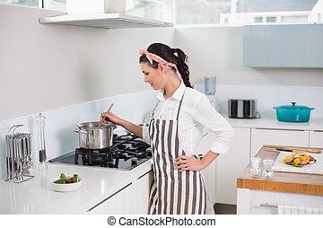 Focused pretty woman cooking in bright kitchen