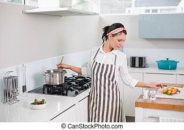 Peaceful pretty woman with apron cooking in bright kitchen