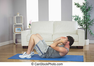 Handsome sporty man doing sit ups in bright living room