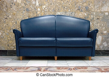 Blue leather sofa with marble wall background