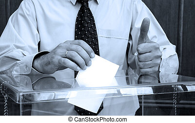 Election - Hand putting a blank ballot inside the box,...