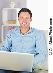 Happy casual man sitting on couch using laptop in bright...