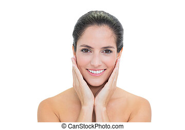 Smiling bare brunette touching her face on white background