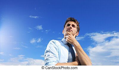 Looking away - Young business man looking up against a blue...