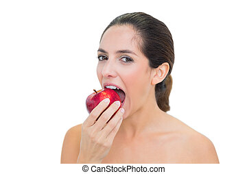 Smiling bare brunette eating red apple on white background