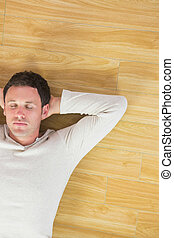 Casual handsome man lying on floor with closed eyes
