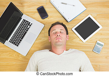 Casual tired man lying on floor in bright room