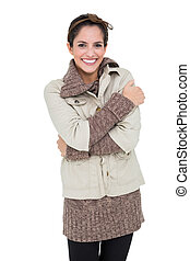 Smiling woman in winter fashion standing cross armed on...