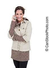Smiling cute brunette in winter fashion phoning