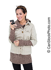 Content cute brunette in winter fashion holding smartphone...