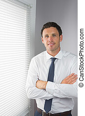 Smiling handsome businessman standing with crossed arms in...