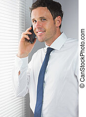 Smiling handsome businessman phoning in room