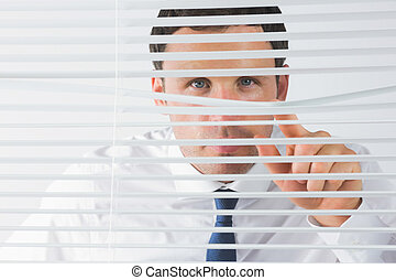 Handsome businessman spying through roller blind