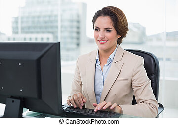 Smiling businesswoman sitting in front of computer in bright...