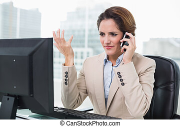 Unhappy businesswoman phoning in bright office