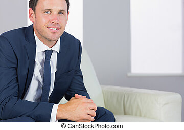 Happy handsome businessman relaxing on couch in bright...