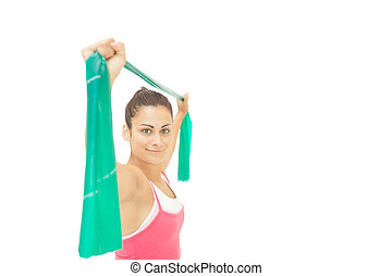 Happy sporty brunette stretching with resistance band on...