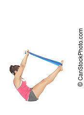 Attractive sporty brunette exercising with resistance band...