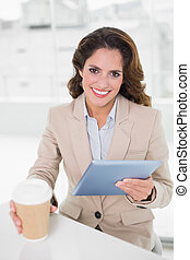 Smiling businesswoman using digital tablet at her desk holding disposable cup in bright office