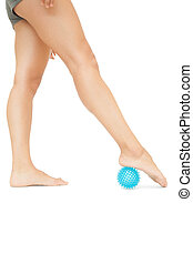 Close up of female legs touching blue massage ball on white...