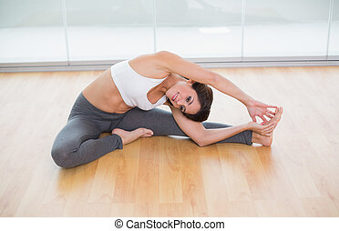 Sporty happy brunette stretching on the floor in bright room
