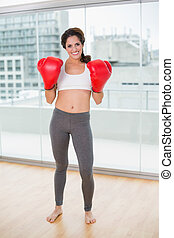 Sporty smiling brunette wearing boxing gloves in bright room