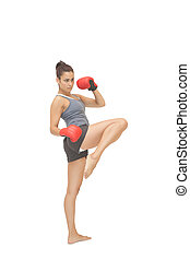 Concentrating sporty brunette kick boxing on white...