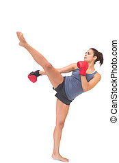 Attractive sporty brunette kick boxing on white background
