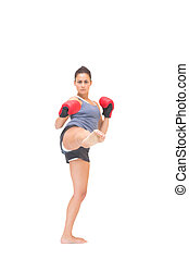 Serious sporty brunette kick boxing on white background