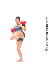 Stern sporty brunette kick boxing on white background