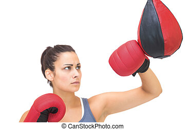 Serious sporty brunette training with punching bag on white...