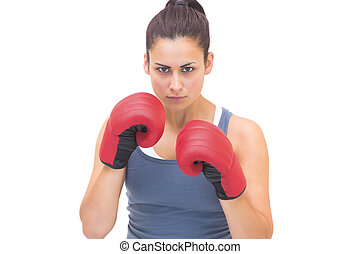 Serious sporty brunette wearing red boxing gloves on white...