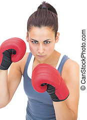 Stern sporty brunette wearing red boxing gloves on white...