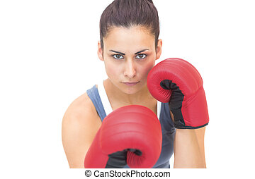 Attractive sporty brunette wearing red boxing gloves on...