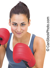 Content sporty brunette wearing red boxing gloves on white...