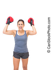 Excited sporty brunette wearing red boxing gloves on white...