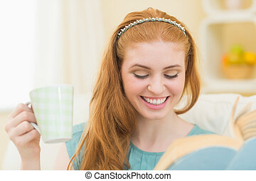 Happy redhead reading a book on the couch and holding mug at...