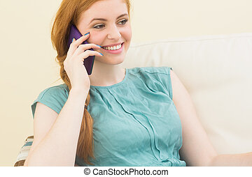 Smiling redhead sitting on the couch making a call